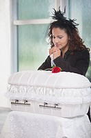 mother grieving at an infant´s coffin