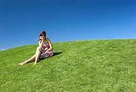 Beautiful woman relaxing on a beautiful green field