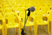 Microphone against yellow chairs