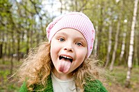 Cheerful little girl in a pink cap puts out the tongue in forestCheerful little girl in a pink cap puts out the tongue in forest