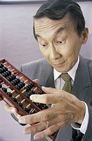 Close_up of a businessman using an abacus