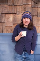 Caucasian Woman Drinking Coffee On A Cabin Porch