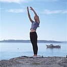 Caucasian Woman Doing Yoga On Lake Shore