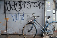 Vintage Bicycle Leaning Against Wall With Graffiti