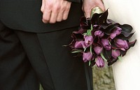 Hands Of Caucasian Bride And Groom Standing With Bouquet