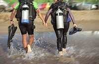 Scuba Diving Couple Walking Out of Ocean Holding Hands