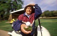 Elderly Man Holding Golf Ball On Tee In Front Of Golf Cart