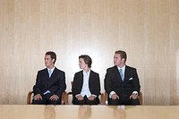Three business people looking in the same direction while sitting together