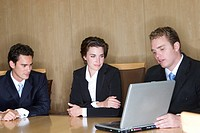 Business man teaches with his laptop two other business people