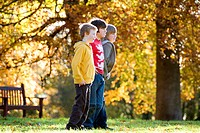 Two boys and a girl standing in a park