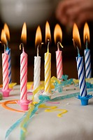 Close_up of burning candles on a birthday cake