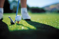 Close_up of a golf club near a golf ball on a tee