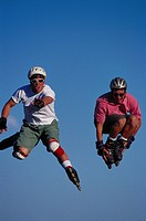 Two young male roller bladders jumping in the air