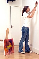 Side profile of a young woman hammering a nail into a wall (thumbnail)
