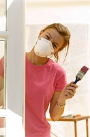 Close_up of a young woman wearing a protective mask and holding a paintbrush