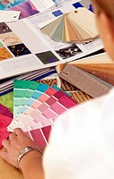 Close_up of a woman looking at shade cards of paints on a table
