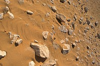 High angle view of stones embedded in sand