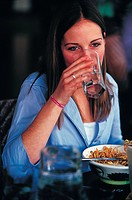 woman sipping glass of water