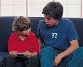 Two boys sharing a video game (thumbnail)