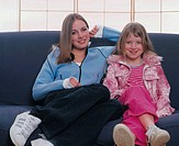 mother and daughter posing on a couch