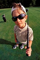 Little boy posing with a golf club (thumbnail)