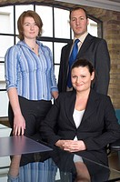 Businesswoman sitting at a table with two business executives standing behind her