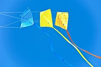 Cape Canaveral, FL - Nov 2008 - Bright yellow and blue triple kite flying in blue sky at Jetty Park in Cape Canaveral, Florida