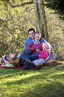 Father, mother and daughter having picnic outdoors