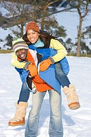 Husband giving wife piggyback ride in snowy field