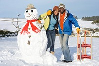Couple with snowman and sled in snowy field