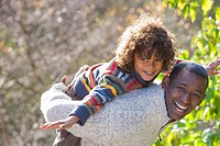 Laughing father giving son piggyback ride outdoors