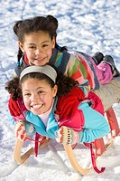 Excited girls sledding down snowy hill on sled