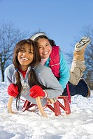 Excited mother and daughter sledding down snowy hill on sled