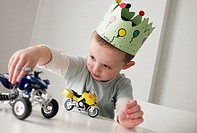 Boy with a crown in his birthday playing with cars on a table (thumbnail)