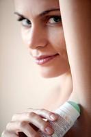 donna si applica il deodorante sotto le ascelle