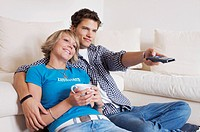 Teenager couple sitting in front of couch and watching television, horizontal format