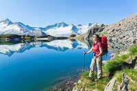 Woman at a mountain lake, Zillertal Alps in the background, Tyrol, Austria, side view