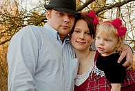 This young Caucasian family is a mother and father wearing a black hat, cuddled together holding their beautiful blond toddler daughter Background is ...