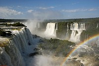 water flowing over iguazu falls with tourists and rainbow brazilian side iguacu national park, parana, brazil, south america
