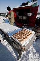 Getting ready to make a winter treat _ a man at a kiosk on the Dufferin Terrace pours hot maple syrup on snow to make taffy in the upper town of the C...