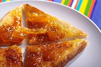 Sliced toast with marmalade on a white plate
