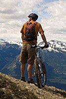Middle aged man prepares to descend Mt Seven on his mountain bike, Golden, BC