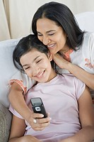 Woman and her daughter text messaging on a mobile phone