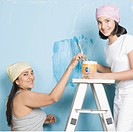 Woman and her daughter painting a wall