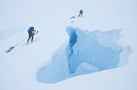Two skiers on an extended ski traverse cross a gaping crevasse in the remote Darwin Range, southern Chile