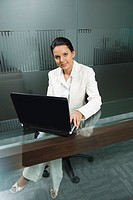 Businesswoman working on a laptop in a board room