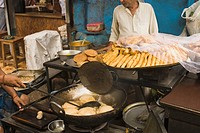 Man frying poori at a food stall, New Delhi, India