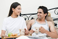 Couple having breakfast on the bed