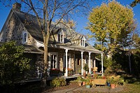 Two story Old Canadiana style Residential Home with landscaped front yard and wicker pation furniture in autumn, Laval, Quebec, Canada. This image is ...
