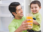 Man carrying his son and holding a glass of orange juice
